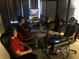 A group of students record a podcast.